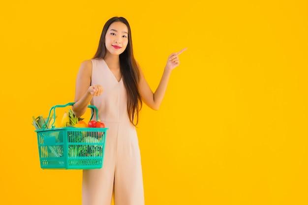 Retrato linda jovem asiática com sacola de compras de supermercado Foto gratuita