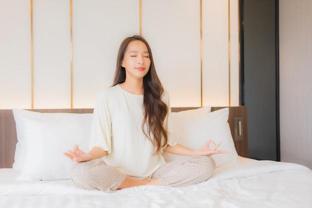Retrato linda jovem asiática meditando na cama, no interior do quarto Foto gratuita