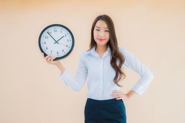 Retrato linda jovem asiática mostrar alarme ou relógio Foto gratuita