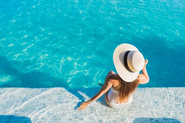 Retrato linda jovem asiática relaxando ao redor da piscina ao ar livre com vista da cidade Foto gratuita