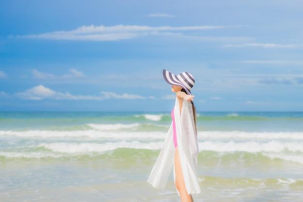 Retrato linda jovem asiática relaxando sorriso ao redor da praia, mar, oceano, numa viagem de férias de férias Foto gratuita