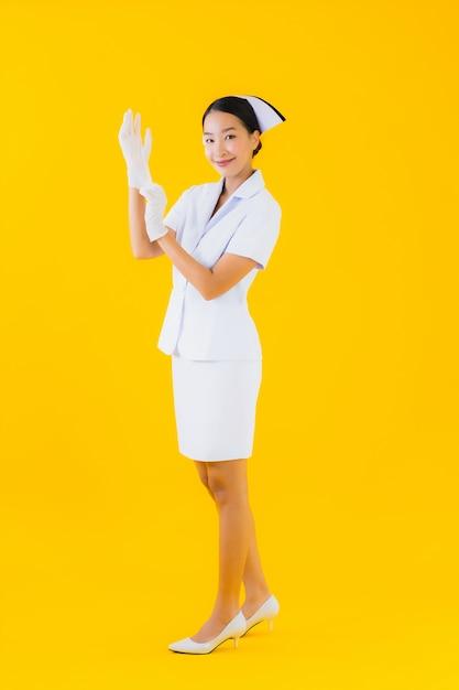 Retrato linda jovem mulher asiática enfermeira tailandesa usar luva Foto gratuita