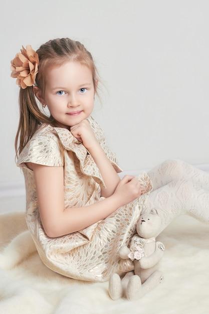 Retrato little girlbeautiful vestido e boneca de brinquedo Foto Premium