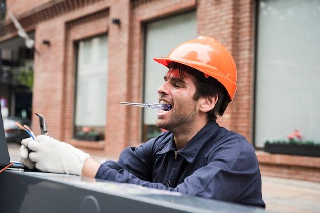 Retrato, macho, eletricista, carregar, verificador, boca, enquanto, trabalhando Foto gratuita