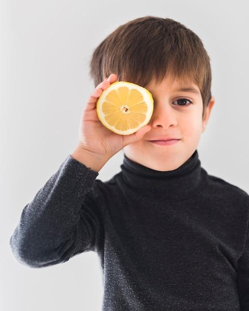 Retrato, menino, segurando, laranja, meio olho Foto gratuita