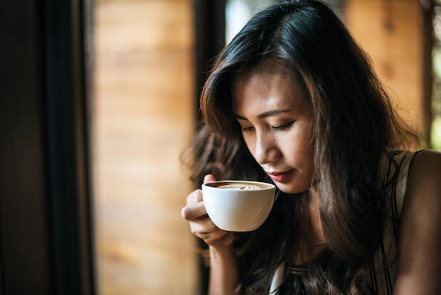 Retrato, mulher asian, sorrindo, relaxe, em, café loja, café Foto gratuita