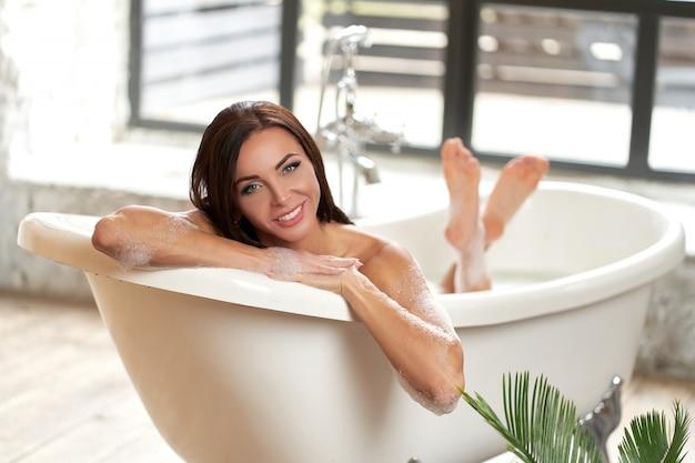 Retrato mulher bonita relaxante deitado na banheira no banheiro Foto Premium