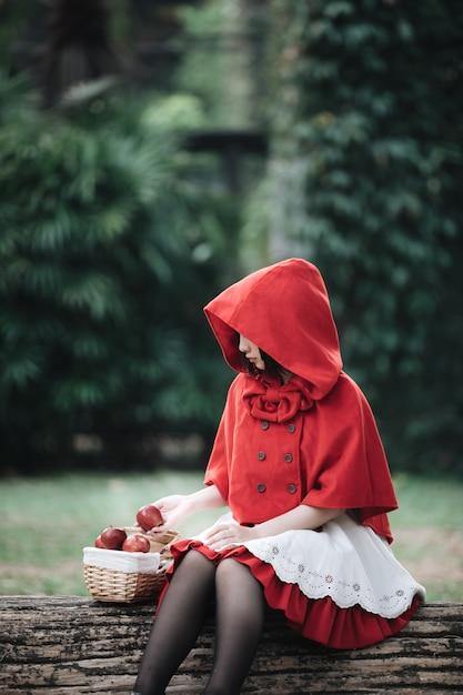 Retrato, mulher jovem, com, pouca roupa vermelha, capuz, traje, em, árvore verde, parque Foto Premium