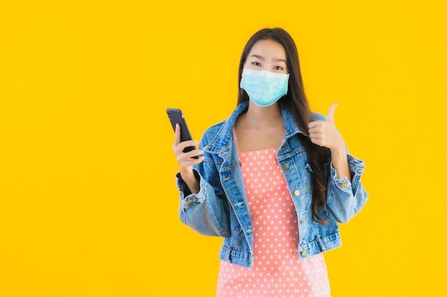 Retrato mulher jovem e bonita asiática usar máscara usar smartphone Foto gratuita