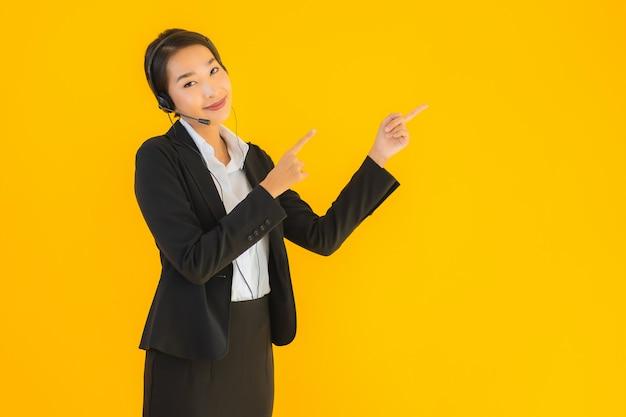 Retrato mulher jovem e bonita negócios asiáticos com fone de ouvido ou fone de ouvido Foto gratuita