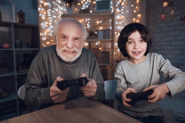 Retrato neto jogar videogame com avô Foto Premium