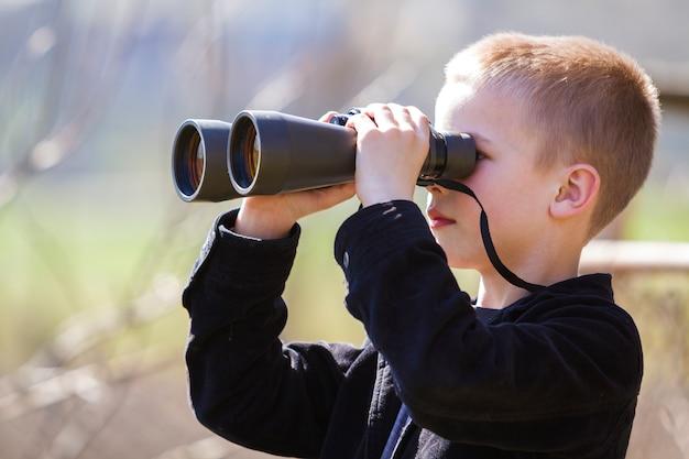 Retrato no perfil do menino loiro bonito bonito olhando pensativamente através de binóculos Foto Premium