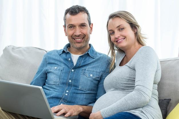 Retrato, par, sentando, junto, sofá, usando, laptop Foto Premium