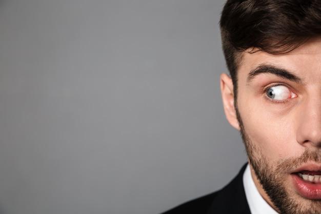 Retrato recortado assustado jovem barbudo olhando de lado Foto gratuita