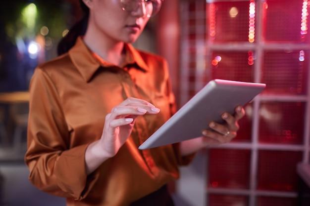 Retrato recortado de uma mulher de negócios asiática contemporânea usando tablet digital enquanto trabalhava no interior de um escritório futurista Foto Premium