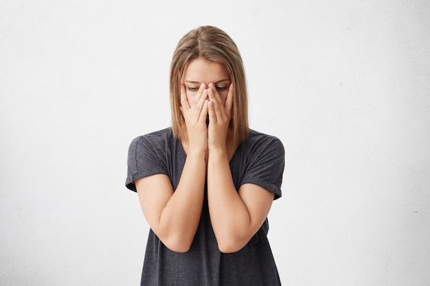 Retrato recortado de uma mulher triste e cansada, cobrindo o rosto com as mãos, tendo os olhos cheios de dor e estresse, tendo fadiga. mulher bonita estressante em pânico, tentando se concentrar e encontrar uma solução. Foto gratuita