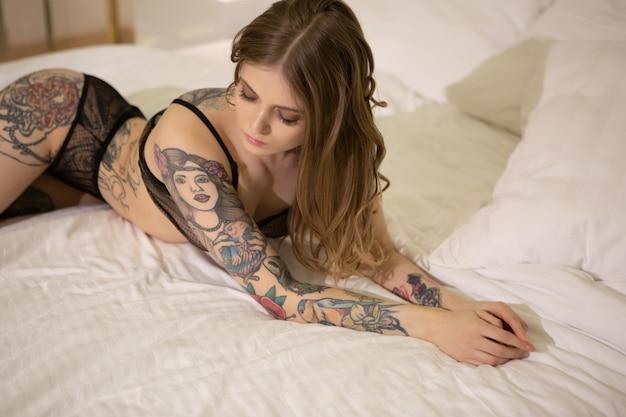 Retrato sensual de uma linda menina loira com tatuagens deitada na cama. Foto Premium