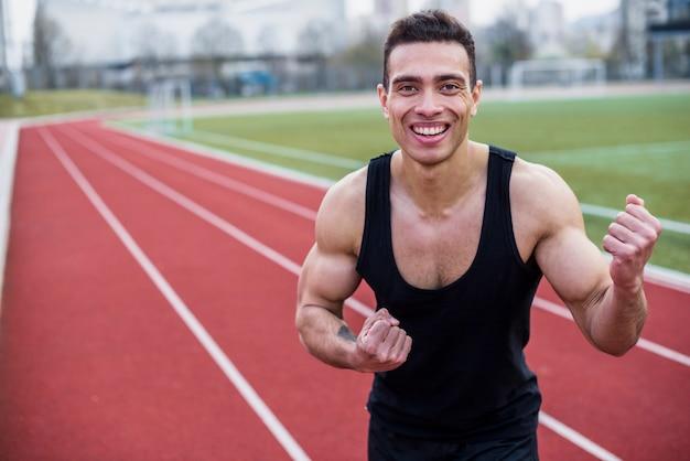 Retrato sorridente de um atleta do sexo masculino, cerrando o punho depois de vencer a corrida Foto gratuita