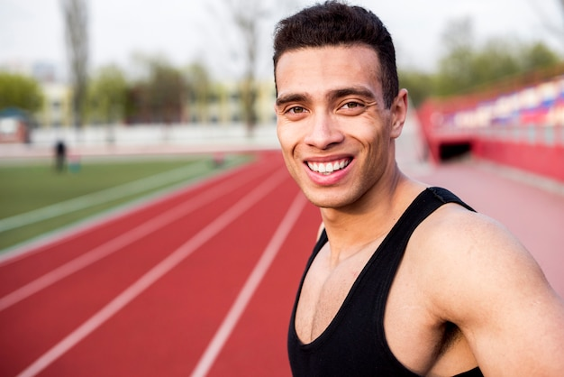 Retrato sorridente de um atleta do sexo masculino na pista de corrida no estádio Foto gratuita
