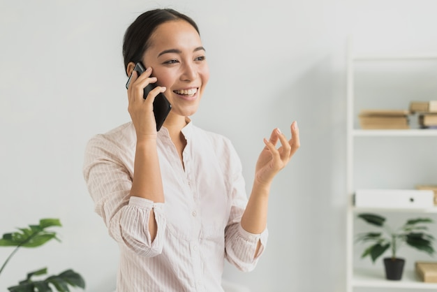 Retrato sorridente mulher falando por telefone Foto gratuita