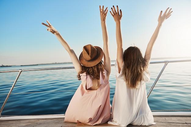 Retrato traseiro de duas fêmeas em vestidos, sentado no lado do iate e acenando, expressando felicidade enquanto olha para o mar. quem mais pode torcer melhor do que um amigo próximo que viaja com você Foto gratuita