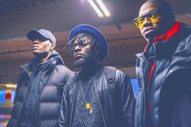 Retrato, três, jovem, homens negros, posar, em, um, estacionamento, lote, olhando Foto Premium