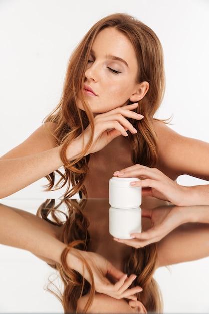 Retrato vertical da beleza da mulher ruiva com cabelos longos e olhos fechados, sentado junto à mesa de espelho com creme corporal Foto gratuita
