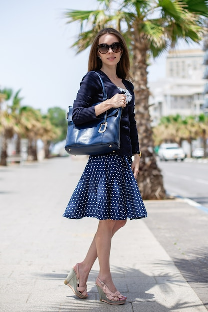Retrato vertical de uma mulher segurando uma bolsa e usando óculos escuros Foto gratuita