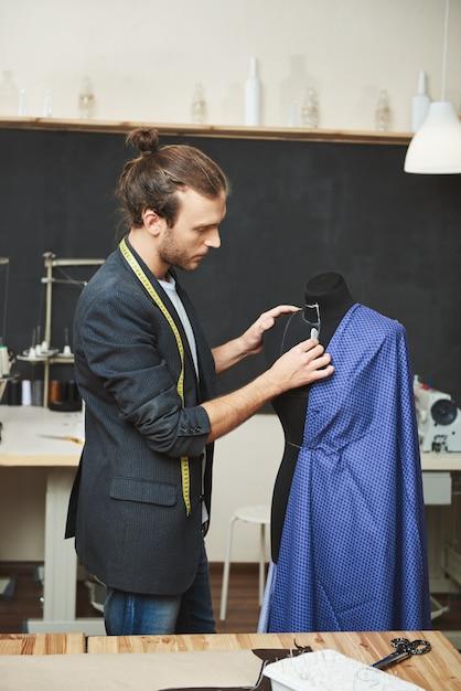 Retrato vertical do designer de roupas hispânico talentoso atraente maduro, preparando o vestido azul para costura, removendo erros no manequim, preparando-se para o desfile de moda Foto gratuita