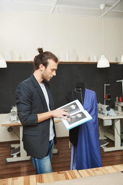 Retrato vertical do jovem alfaiate masculino profissional bem sucedido trabalhando no vestido azul para o cliente, lembrando algumas técnicas de costura, olhando através do livro tutorial. Foto gratuita