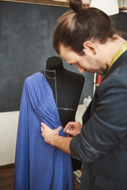 Retrato vertical do jovem designer masculino bem sucedido e bonito na jaqueta elegante, olhando como ficará a dobra neste tipo de tecido no manequim, preparando-se para o desfile de moda Foto gratuita