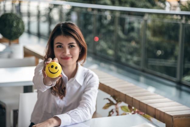 Retratos da bela mulher asiática garante confiança é segurar bola de sorriso enquanto está sentada. Foto Premium