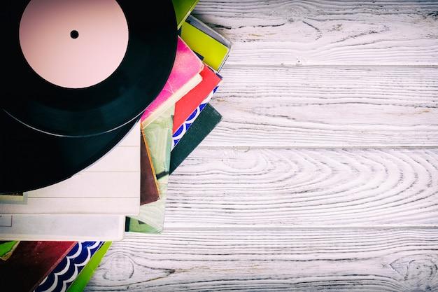 Retro estilo imagem de uma coleção de antigos discos de vinil lp com mangas em um fundo de madeira com cópia espaço vista superior em tons Foto Premium