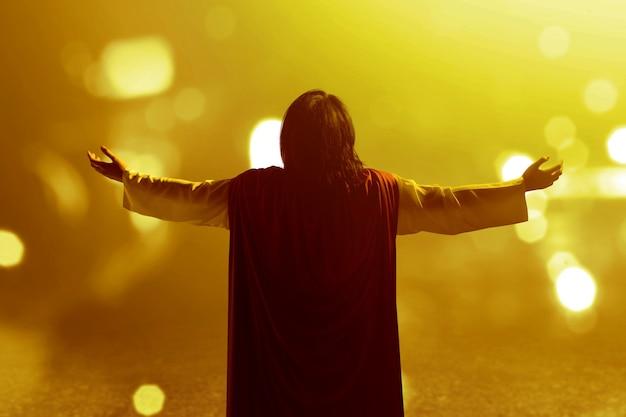 Retrovisor de jesus cristo levantou as mãos e orando a deus Foto Premium