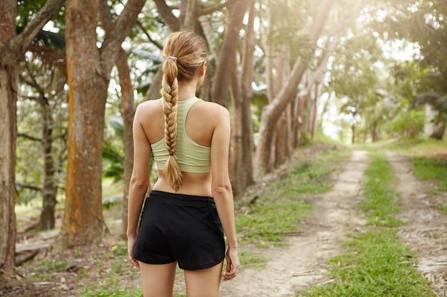Retrovisor do atleta jovem com corpo apto vestindo sutiã esportivo e calção preto sozinho na trilha na floresta tropical determinado a correr. Foto gratuita