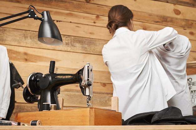 Retrovisor do designer bem sucedido ocupado do manequim de vestir vestuário enquanto trabalhava na oficina sobre novas roupas para sua loja, usando a máquina de costura. mulher com imaginação e hobby interessante Foto gratuita