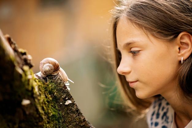 Reunião alegre de uma menina e um caracol. Foto Premium