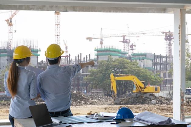 Reunião de engenheiro e trabalhador, discussão com plano de construção no local de trabalho e ponta do dedo no local de trabalho Foto gratuita