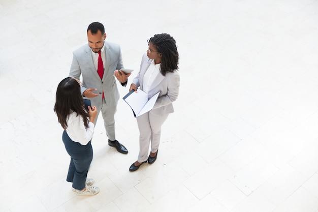 Reunião de equipe diversificada de negócios no corredor do escritório Foto gratuita