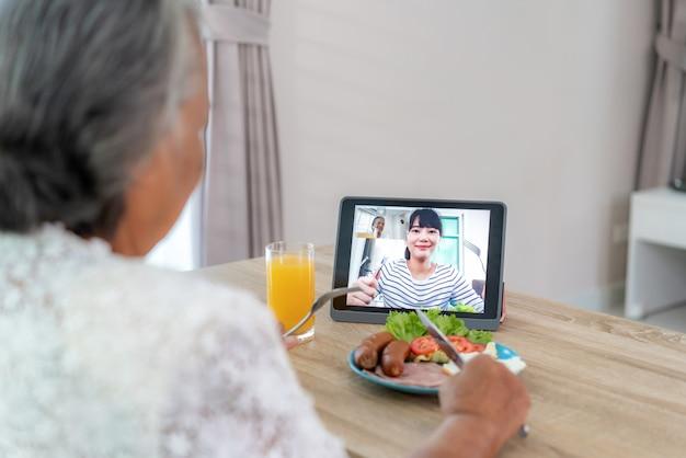 Reunião de happy hour virtual de mulher idosa asiática e comer comida on-line junto com a filha em videoconferência com tablet digital para uma reunião on-line em videochamada Foto Premium