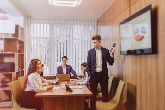 Reunião dos trabalhadores de escritório à mesa, olhando a apresentação com diagramas na tv Foto gratuita