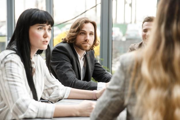 Reunião em andamento. dois funcionários de escritório estão olhando para o colega com expressão de surpresa no rosto Foto Premium