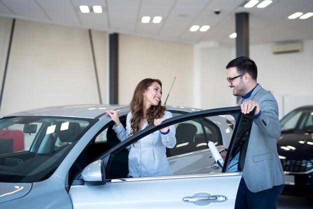 Revendedor de automóveis e cliente no showroom de veículos escolhendo um carro novo Foto gratuita