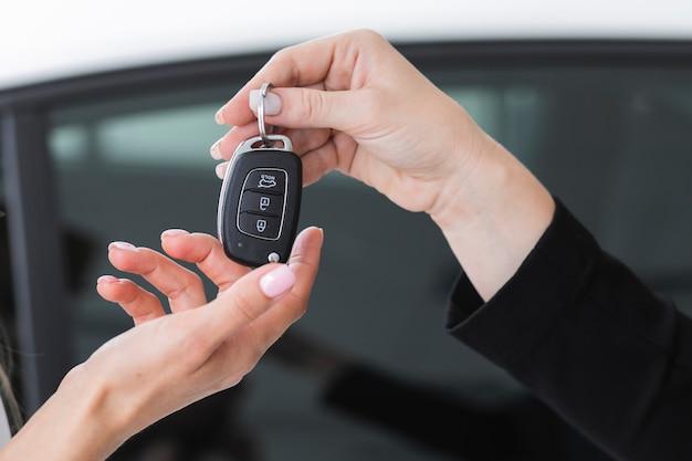 Revendedor feminino, oferecendo as chaves de um carro Foto gratuita