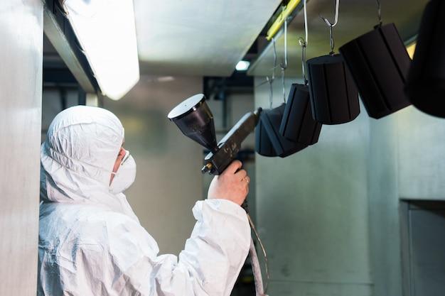 Revestimento em pó de peças metálicas. um homem em um traje de proteção sprays de tinta em pó de uma arma em produtos de metal Foto Premium