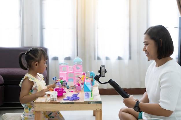 Revisão da mãe e da filha que joga brinquedos em casa. com gravação fazendo video Foto Premium