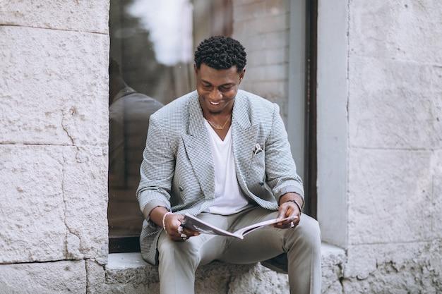 Revista de leitura de homem afro-americano Foto gratuita