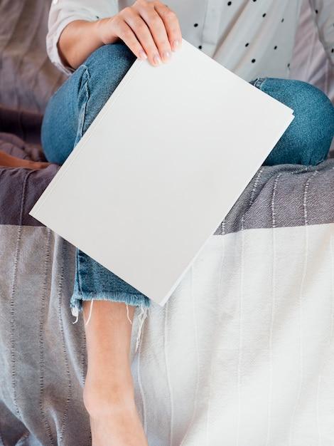 Revista em branco de close-up realizada por uma mulher Foto gratuita