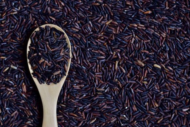 Riceberry (baga de arroz), que é uma variedade de arroz registrada da tailândia em colher de pau em Foto Premium
