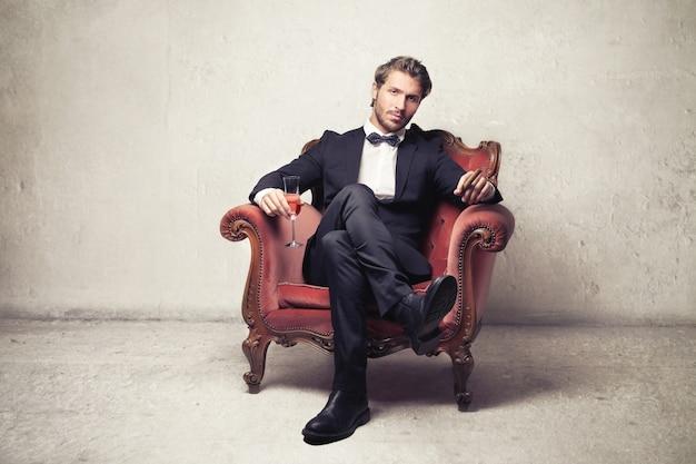 Rico homem elegante, sentado em uma poltrona Foto Premium